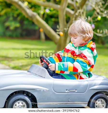 Little preschool boy palying with big toy old vintage car and having fun, outdoors. Active leisure with kids outdoors  on warm spring or autumn day. - stock photo