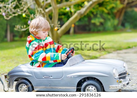 Little preschool boy playing with big toy old vintage car and having fun, outdoors. Active leisure with kids outdoors  on warm spring or autumn day. - stock photo