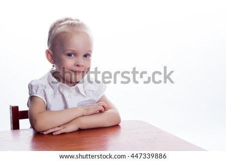 Little preschool girl sitting at the table preparing for the lesson. Isolated on white background  - stock photo