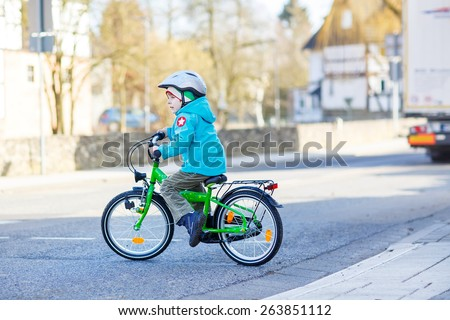 Little preschool kid boy biking with bicycle over the road in the city. Happy child in colorful clothes. Active leisure for kids outdoors. - stock photo