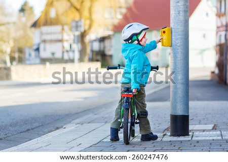 Little preschool kid boy riding with his first green bike in the city. Happy child in colorful clothes standing near traffic lights. Active leisure for kids outdoors. - stock photo
