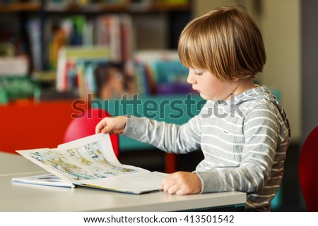 Little preschooler boy of 5 years old reading book in the library - stock photo
