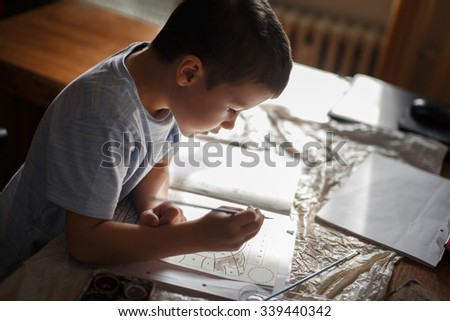 Little preschooler boy painting coloring book at home - stock photo