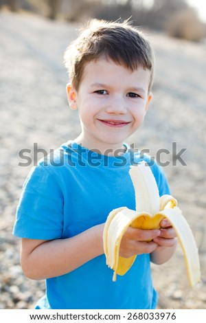 Little preschooler boy with banana, outdoor portrait - stock photo