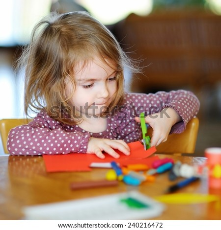 Little preschooler girl cutting colorful paper - stock photo