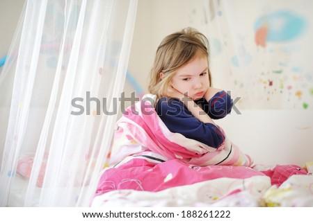 Little preschooler girl in pajamas on sunny morning - stock photo