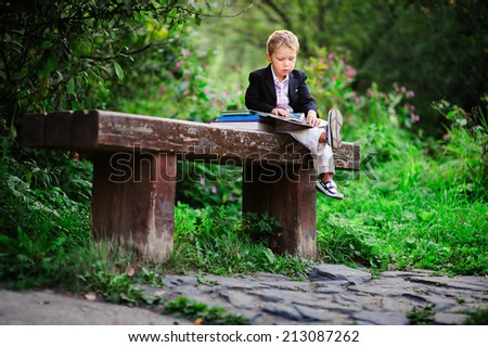 Little preschooler kid reading outdoor