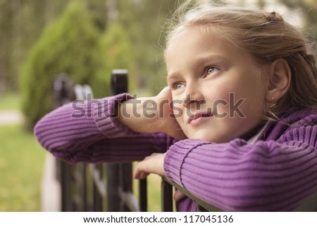 Little preteen girl staring into infinity outdoor in park at autumn - stock photo