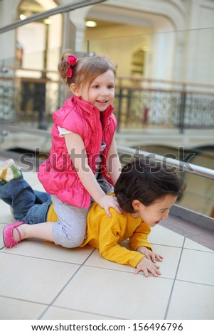 Little pretty girl and boy play on floor in big mall. Girl saddled lying boy.