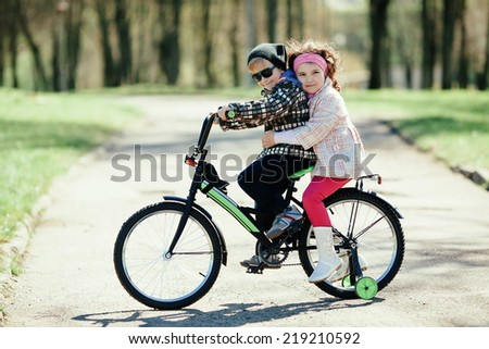 little pretty girl and cute boy riding on bicycle together - stock photo