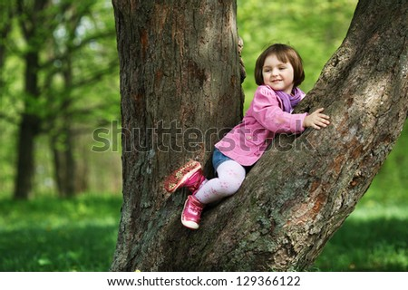 little pretty girl climbing tree in the park