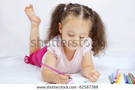 little pretty girl draws with markers on a white background isolated - stock photo