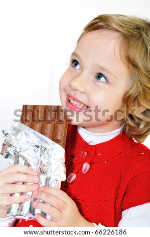 little pretty girl eating big chocolate bar - stock photo