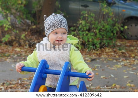 Little pretty girl in vest sits on wooden motorbike on playground at sunny day - stock photo