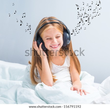 little pretty  girl listening to music at home in white bed - stock photo