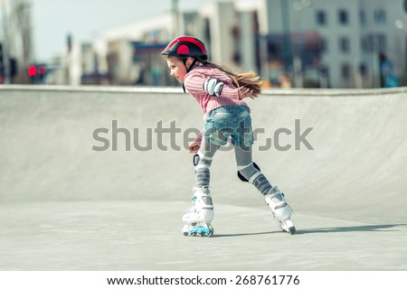 Little pretty girl on roller skates in helmet at a park. back view