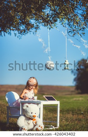 little pretty girl outdoors at a table - stock photo