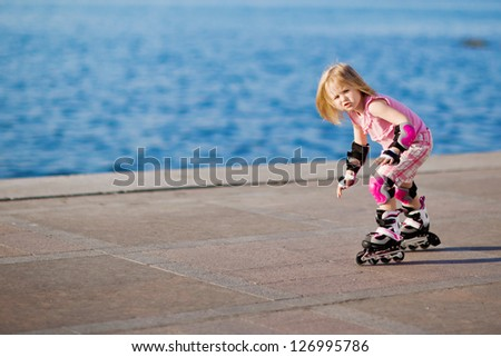 little pretty girl riding a roller - stock photo