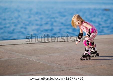 little pretty girl riding a roller - stock photo