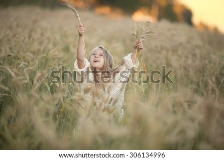 little pretty girl with long blond hair standing in the field of wheat of corn with her hands up to the sun at summer time - stock photo