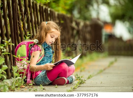 Little pretty schoolgirl reading a book sitting on the street - stock photo