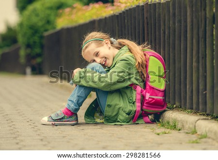 Little pretty schoolgirl  sitting on the street with her backpack - stock photo