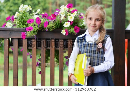 Little pretty schoolgirl with  books near  fence with flowers - stock photo