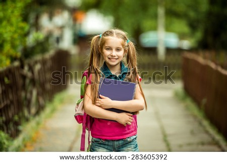 Little pretty schoolgirl with the book on the street - stock photo