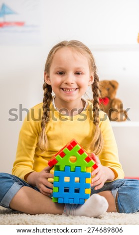 Little pretty smiling girl in yellow  pullover holding lego house. - stock photo