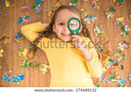 Little pretty smiling girl in yellow  pullover laying on the floor and playing with puzzle and loupe. - stock photo