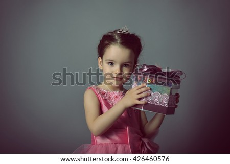 Little Princess holding gift box. Beautiful girl with present. Little lady. Holiday, birthday, New Year, Christmas concept.  - stock photo