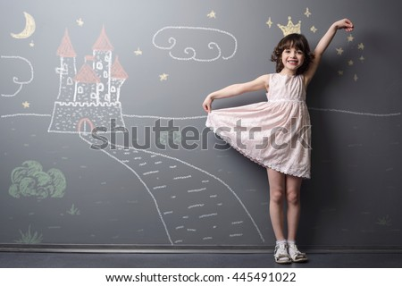 Little princess near her castle smiles and holds her dress with hand. Depicted road, crown and stars on the neutral background. True emotion of happiness of the child. - stock photo