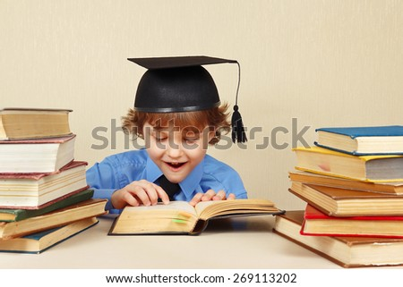 Little professor in academic hat reading an old books - stock photo