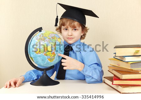 Little professor in academic hat showing on the globe among the old books - stock photo