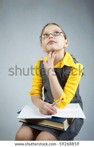 Little pupil girl with book. Sitting and writing - stock photo