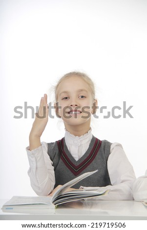 little pupil sitting at a desk and pulls arm - stock photo