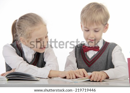 little pupils sitting at a desk - stock photo