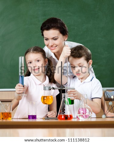 Little pupils study chemistry with their teacher at laboratory class - stock photo