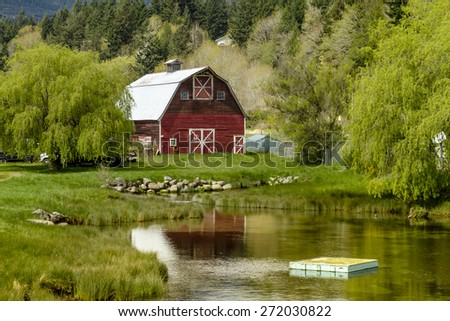 Little red barn reflecting in small pond surrounding by weeping willow trees in rural coastal setting along Pacific Coast Highway 101 on sunny spring morning - stock photo