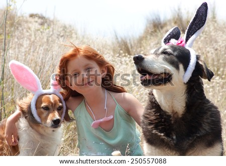 little red haired girl dressing her pet dogs up as easter bunnies for an easter egg hunt outdoors