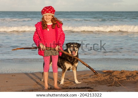 little red haired girl playing on a beach with her dogs  - stock photo