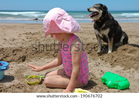 little red headed girl in pink bathing suit on beach making sand castles with her pet dog sitting nearby - stock photo