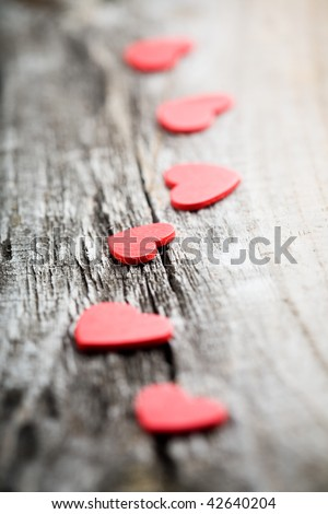 Little red hearts on old wooden background - stock photo