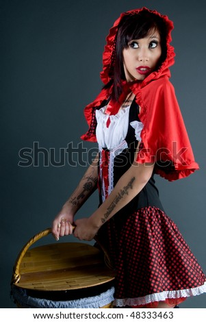 little red riding hood carrying a basket - stock photo