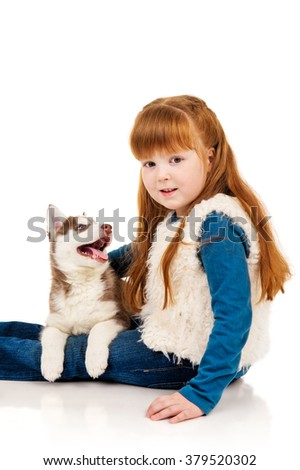 Little redhead girl with a puppy husky - stock photo