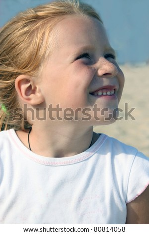 Little Redhead girl with freckles, looks into the blue sky - stock photo