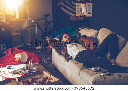 Little rest can help with hangover. Young handsome man lying down on sofa and napping in messy room after party - stock photo