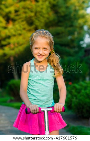 Little rider dressed up in bright pink and blue clothes. Close-up portrait of a beautiful caucasian blonde child. Nice idea of a hairstyle for little princesses. - stock photo