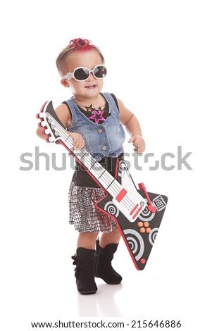 Little Rock Star.  Adorable toddler dressed as a punk rock star and plying with a toy guitar.  Isolated on white. - stock photo