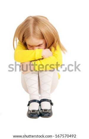 Little sad and upset child sitting hunched up into a ball. Isolated on white background - stock photo